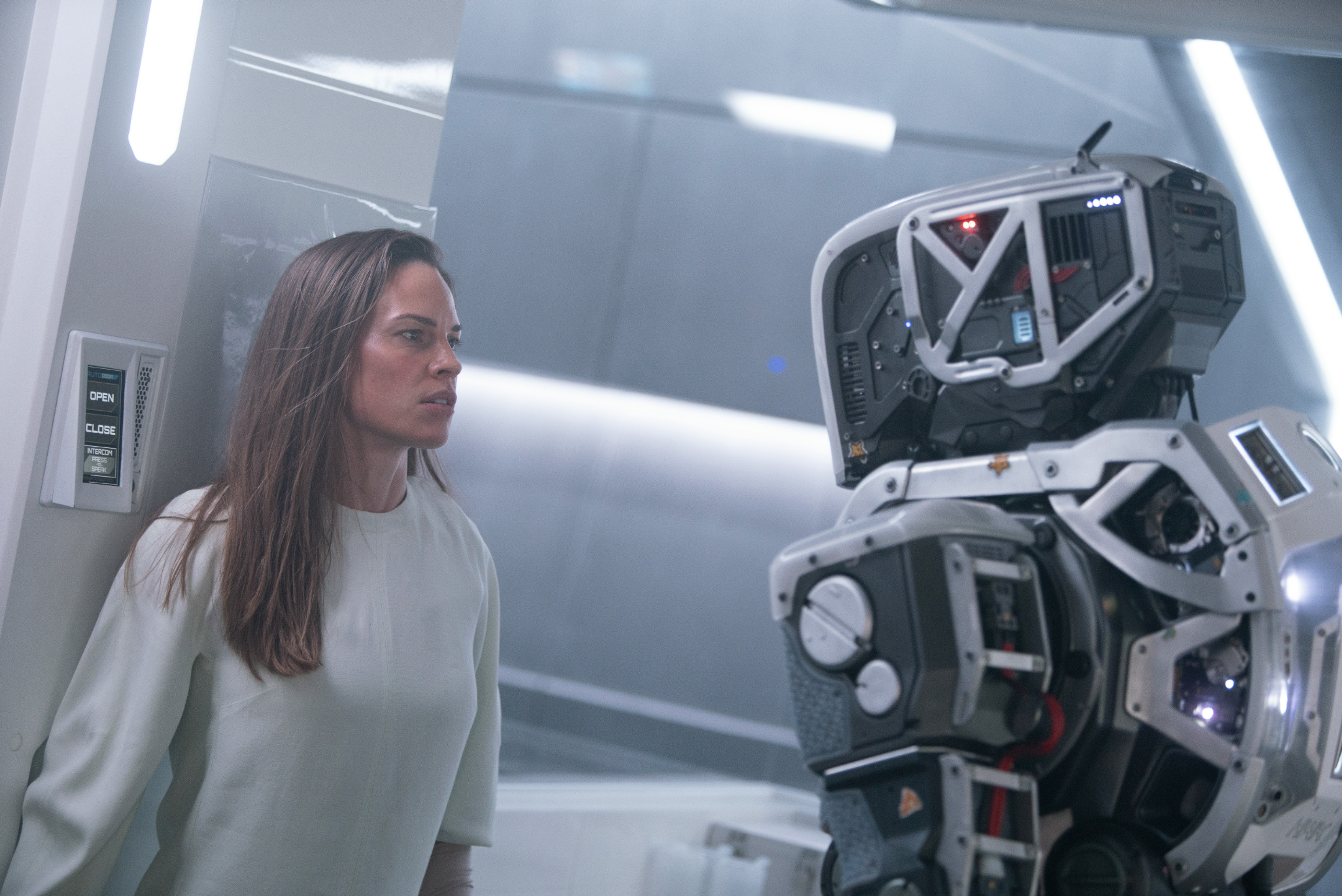 Hilary Swank's character is up against a wall, looking scared of 'Mother' Android