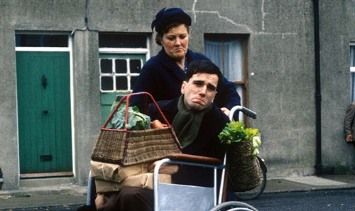 Daniel Day-Lewis in the film My Left Foot. He is sitting in a wheelchair with a basket of food on his lap, a woman is behind him.