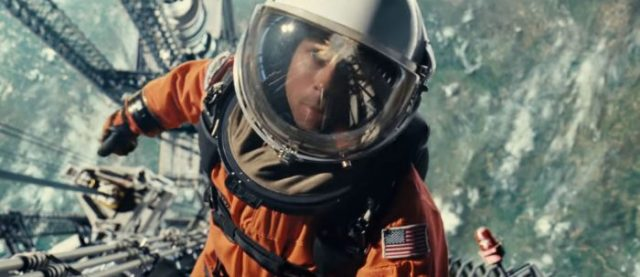 Brad Pitt is wearing an astronaut suit and he is floating in a space vessel, looking at the camera