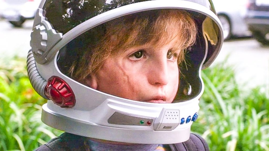 a close up of Auggie's face, he's wearing a spaceman helmet