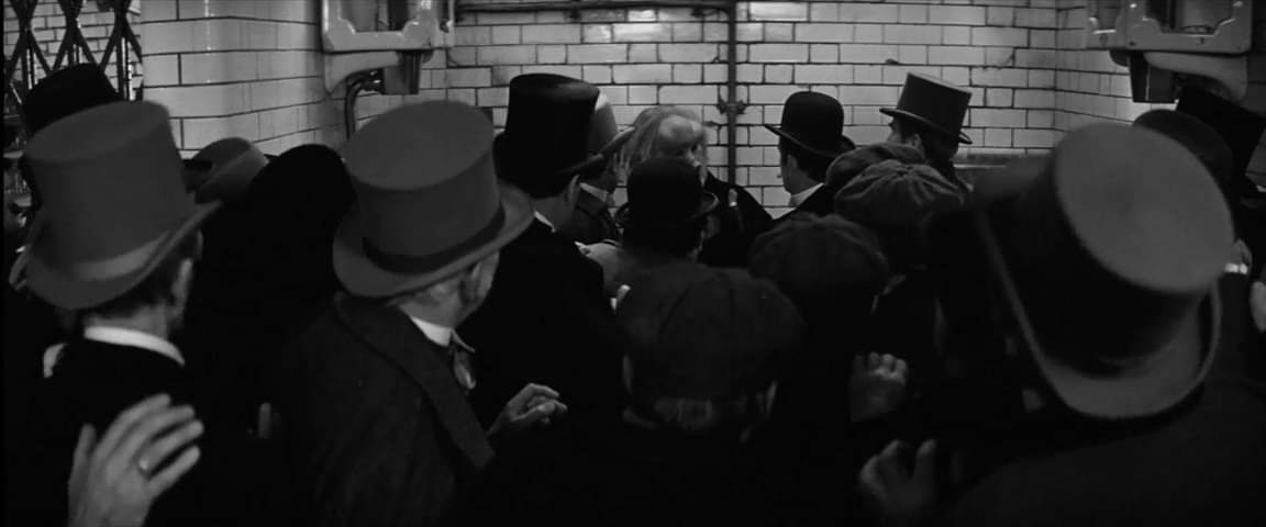 Black and white photo of John Hurt as the elephant man cornered by a crowed of Victorian era men