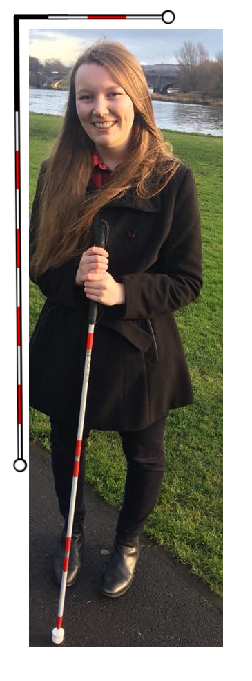 This is a photo of Charlotte, smiling. She is standing in from of a lake wearing a black coat and holding a cane for the blind. There are red and white cane graphics around the edges of the photo.