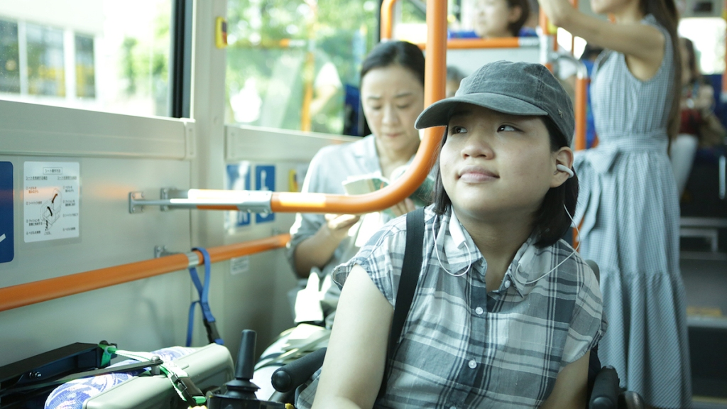 Still from the film 37 Seconds. A young woman with black hair is sitting in her powerchair on the bus. She's wearing a baseball cap and is looking outside the window with a content expression on her face.