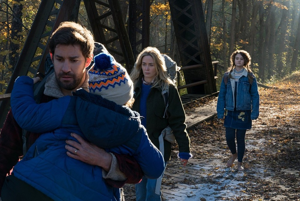 Still from the film A Quiet Place. A man holding a young boy, a woman, and a young girl are all walking in a line facing the camera. They're wearing jackets and backpacks, and the background is a forest landscape.