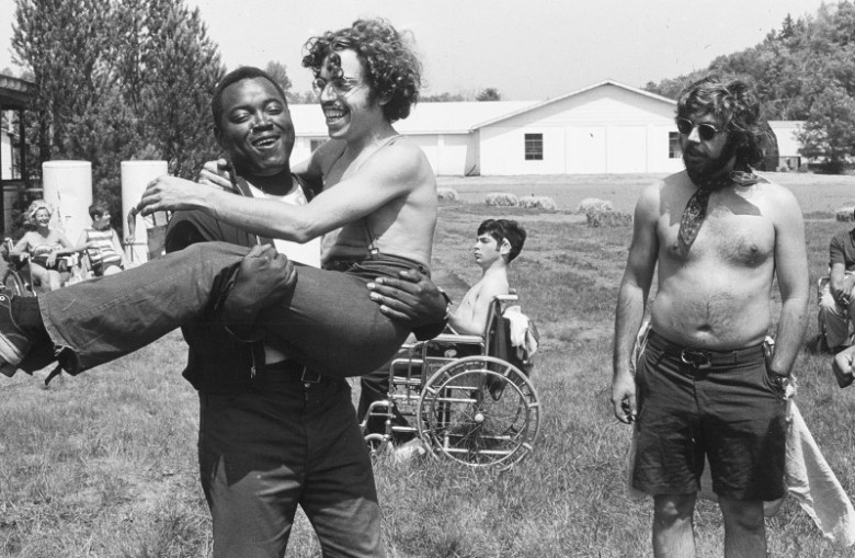 Still from the documentary Crip Camp. This is a vintage black and white photo of a Black man holding a shirtless white man, and they're both laughing. A white shirtless man with one hand is next to them, and a shirtless white man in a wheelchair is behind them. They are on a field and there is a white cabin like building in the background.
