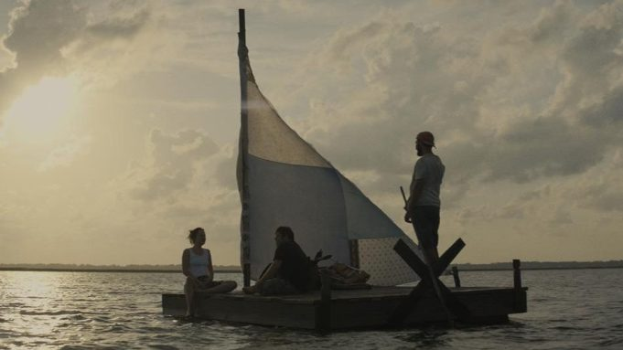 Still from the film The Peanut Butter Falcon. Two men and a woman are on a makeshift sailing boat in a body of water. The sun is setting.