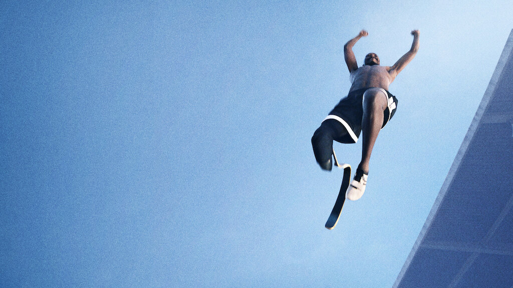 Still from the documentary Rising Phoenix. A from the ground shot of a Black man with one leg and a blade jumping in the air. The sky is a vast blue.